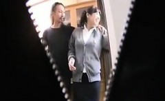 Busty young Asian in a gray sweater stands between two guys
