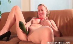 Mature blonde masturbates with a cucumber